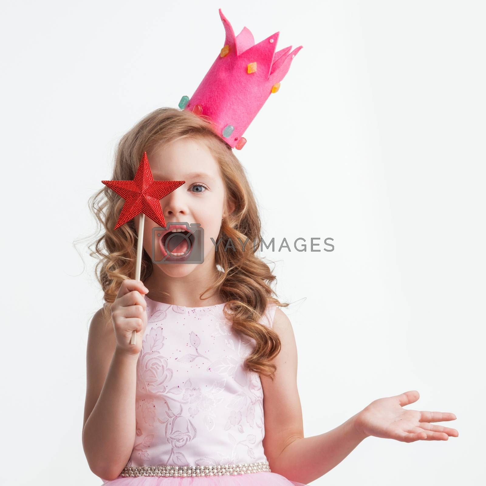Beautiful little candy princess girl in crown holding star shaped magic wand and making a wish spell isolated on white background
