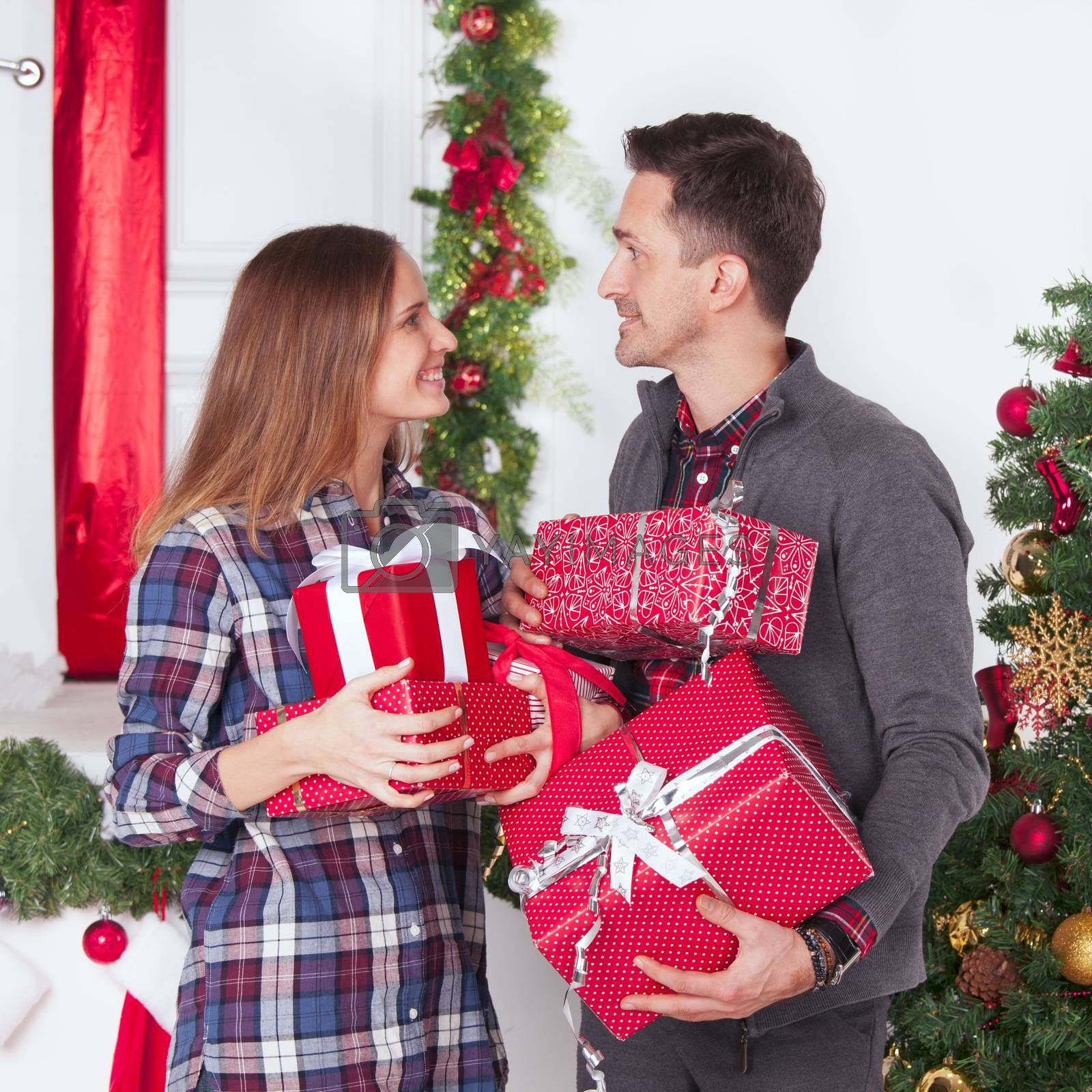 Couple in love sitting next to a nicely decorated Christmas tree, hloding Christmas gifts and smiling