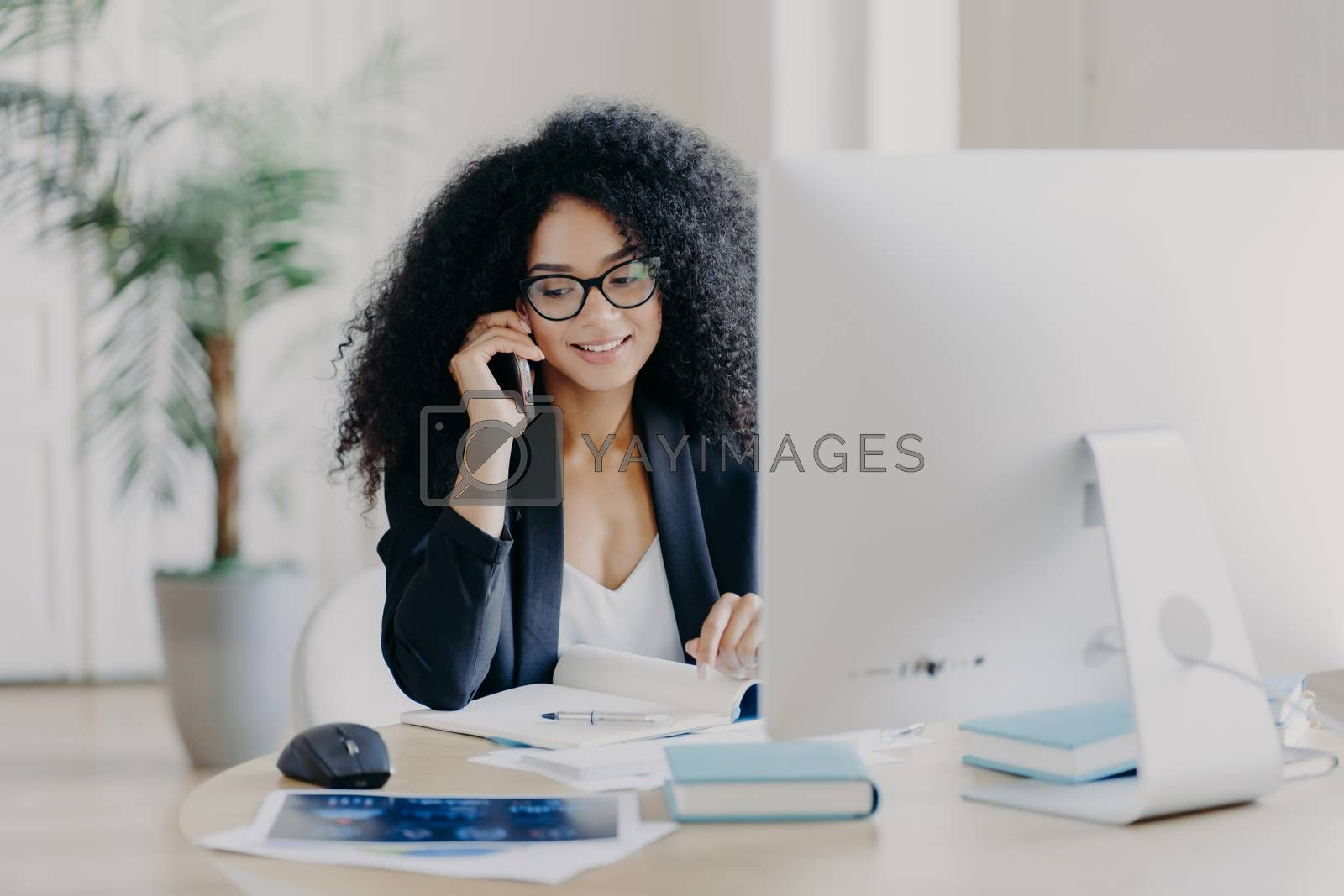 Photo of satisfied Afro American woman calls via smartphone, makes notes in notepad, involved in working process, sits at desk with computer, wears spectacles, formal clothes, has phone communication