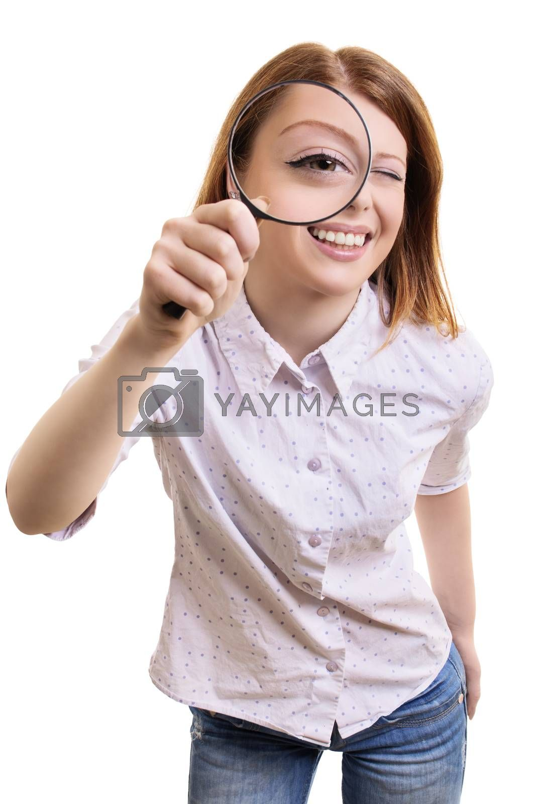 Close up portrait of a cheerful pretty young woman looking at camera through magnifying glass, isolated on white background.