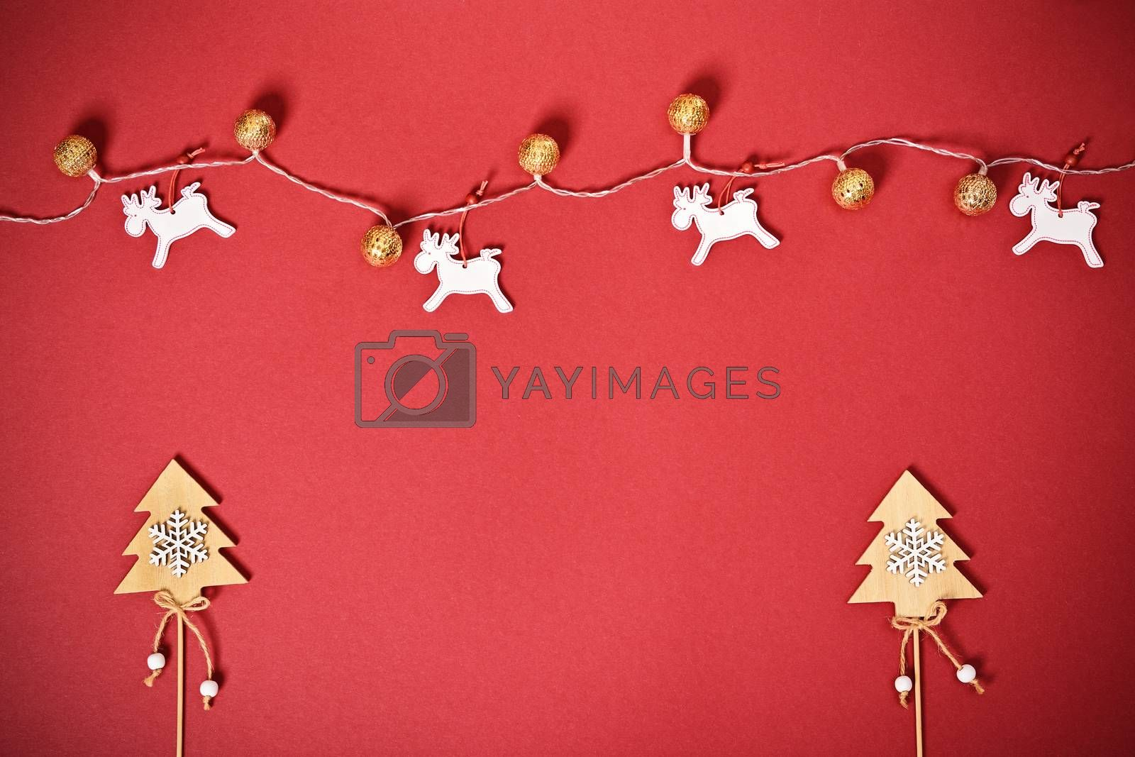 Christmas and New Year composition. Seasonal greeting card concept with Christmas trees, lights and reindeer on red background. Christmas, winter, new year concept. Flat lay, top view, copy space.