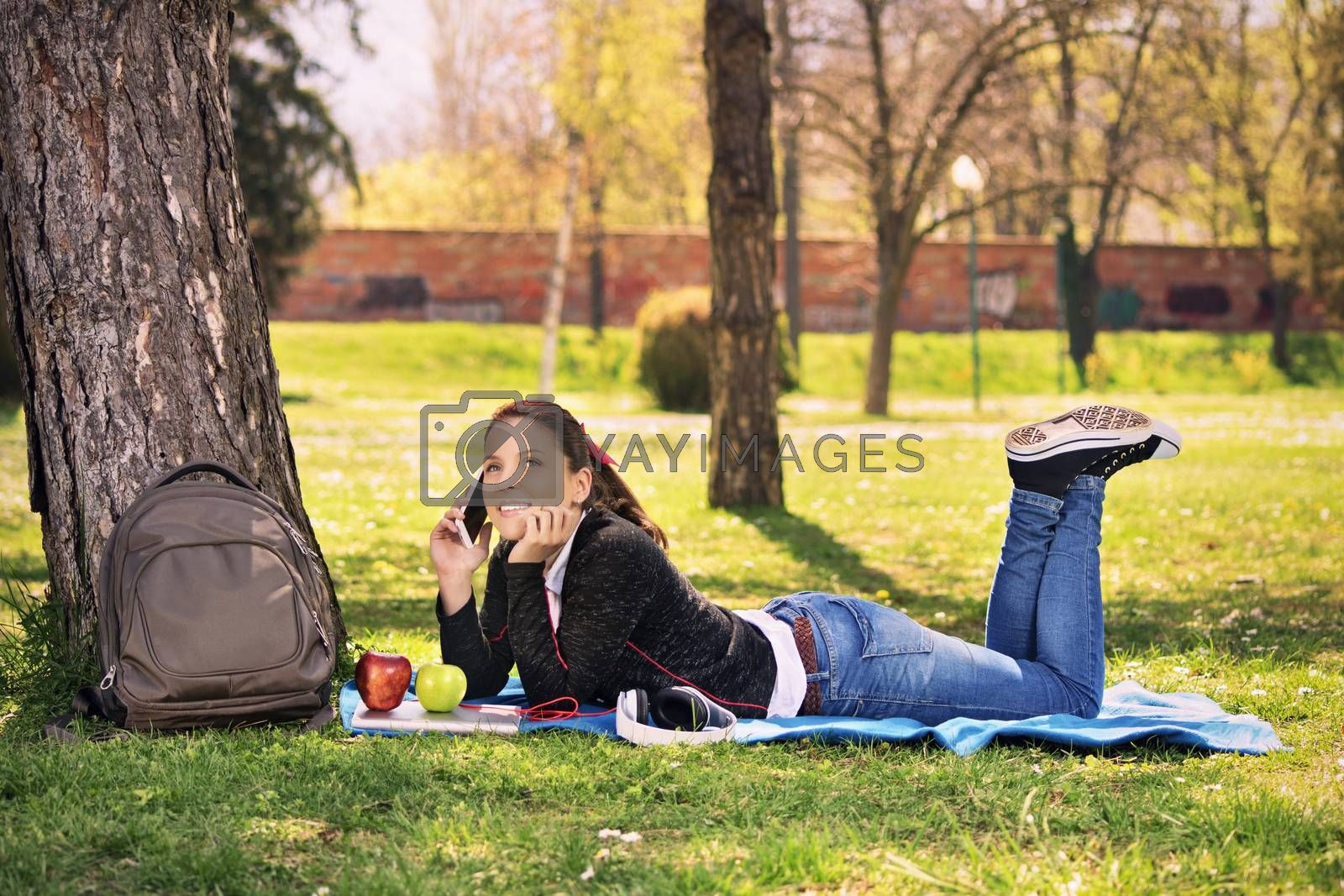 Young girl in a park talking on the phone by Mendelex