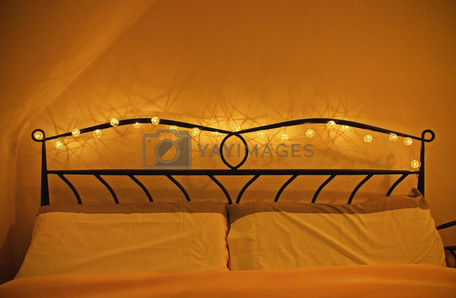 Coziness, comfort, interior and holidays concept. Bedroom interior with comfortable bed and pillows, garland of Christmas lights around the wrought iron headboard. Valentine's day date concept.