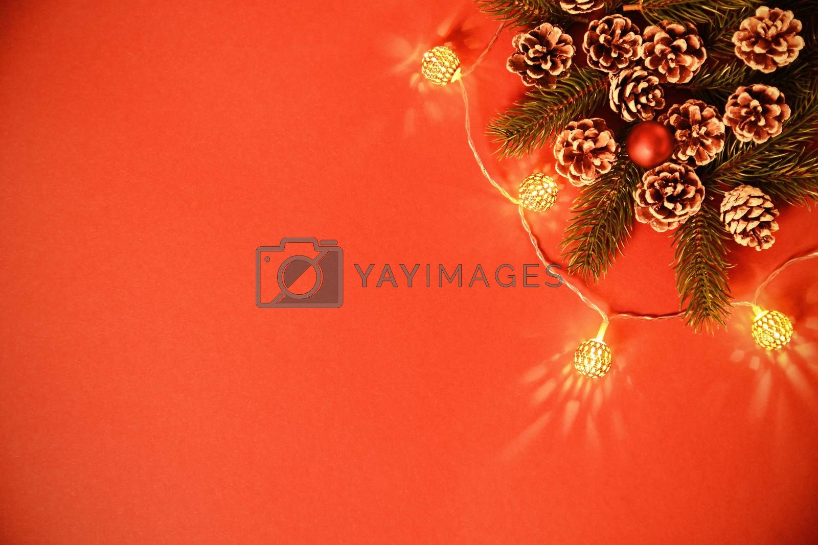 Christmas and New Year composition. Seasonal greeting card concept with pinecones, evergreen branches and lights on red background. Christmas, winter, new year concept. Flat lay, top view, copy space.