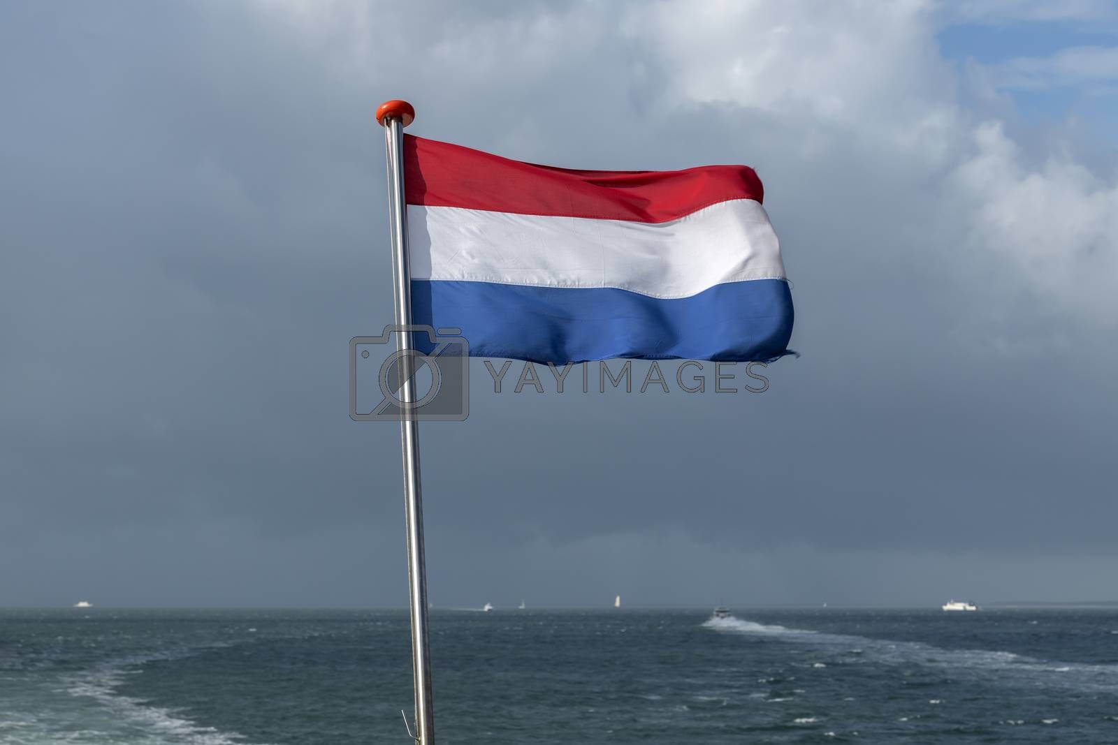 Wadden Sea with red white blue Dutch flag and ships in the background