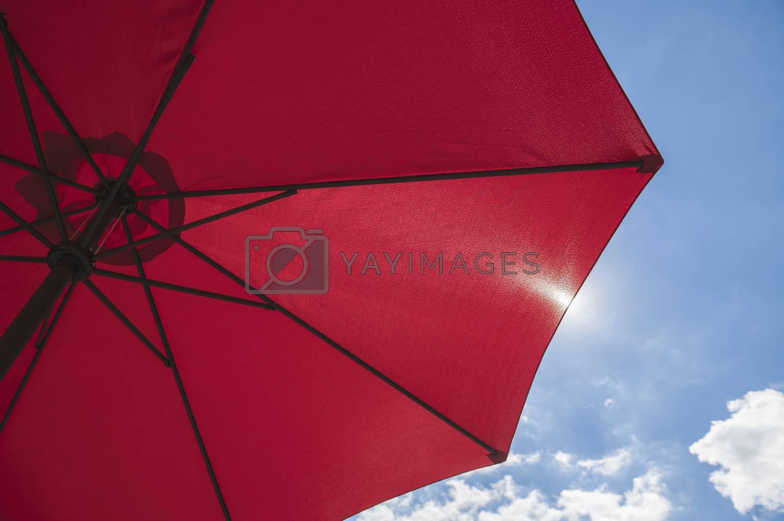 Red beach parasol against a blue sunny summer sky