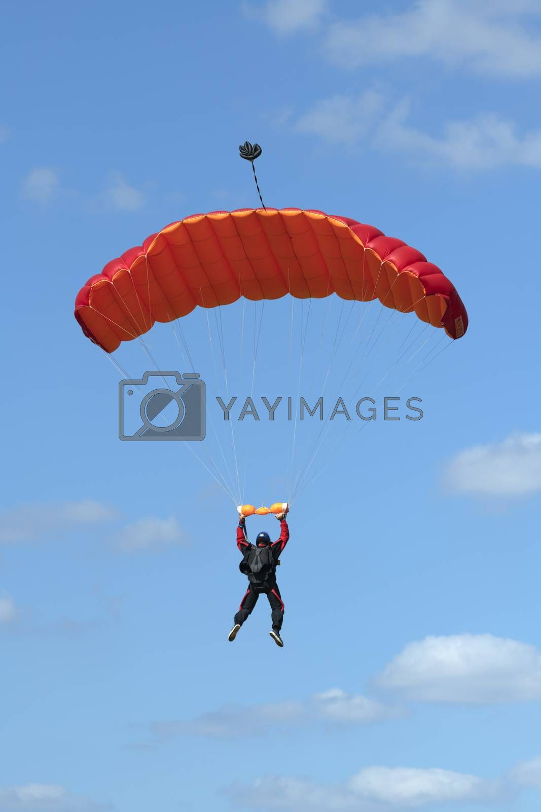 Parachutist floating to a red square-shaped parachute