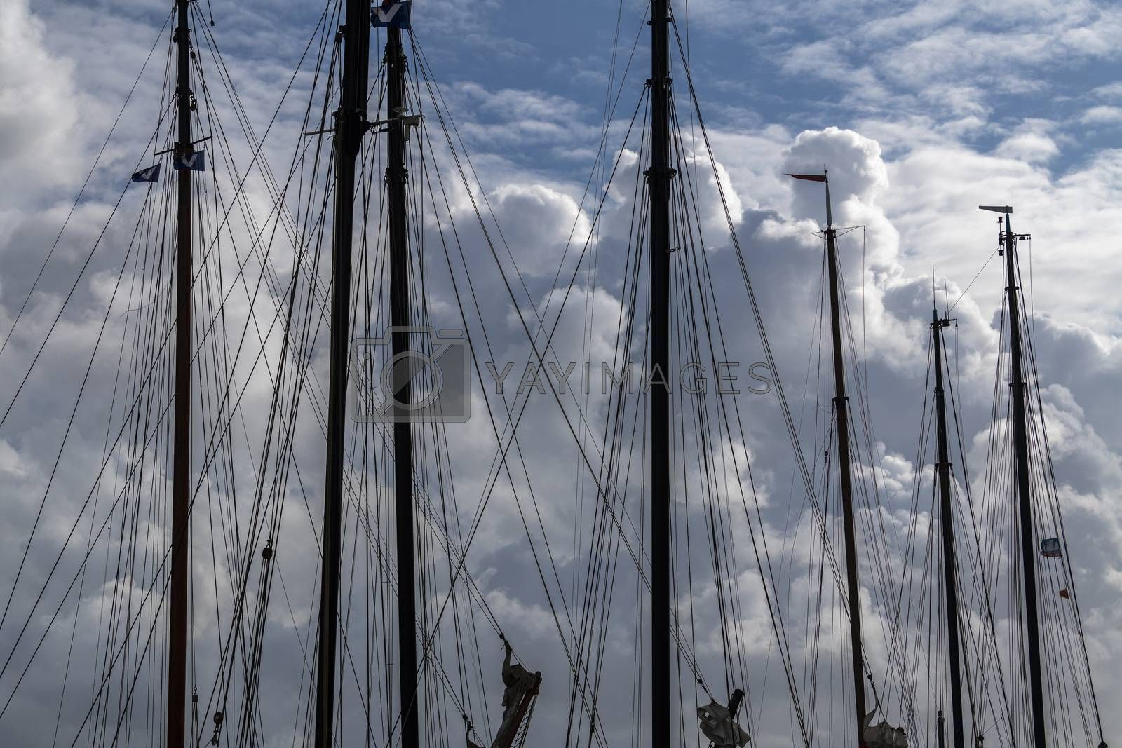 Masts in a harbor with impressive cloudy skies in the background in the North of the Netherlands