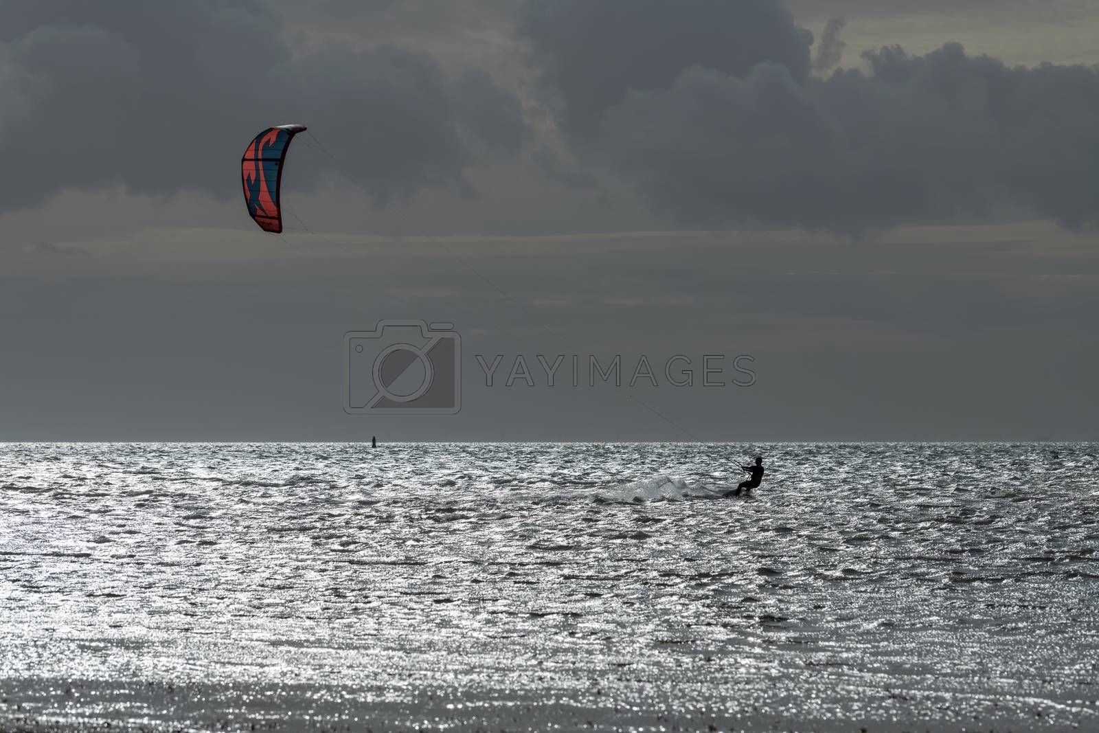 Sports kite surfer in the evening sun on the Wadden Sea near the island of Terschelling in the North of the Netherlands