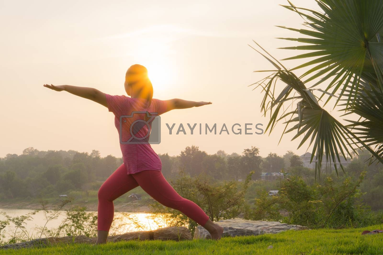Asian woman practicing yoga in a garden. Healthy lifestyle and r by mikesaran