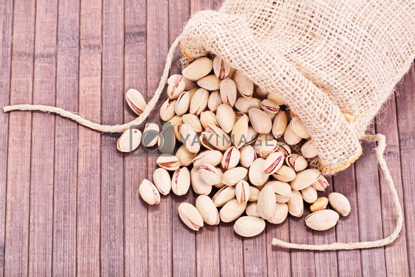 Close up shot of pistachios in a burlap sack spilled on wooden background.