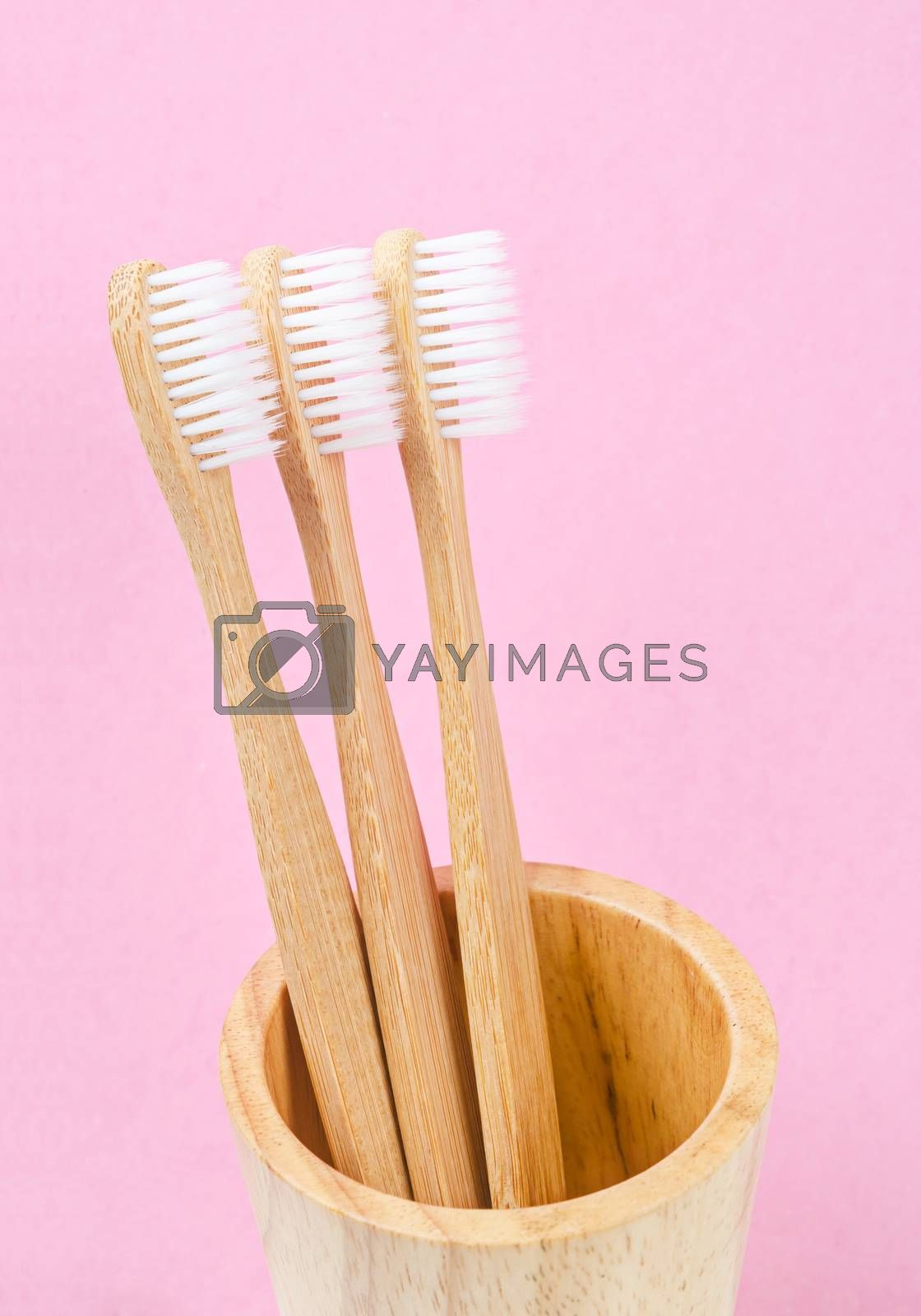 Bamboo toothbrushes on pink background. Zero waste concept.