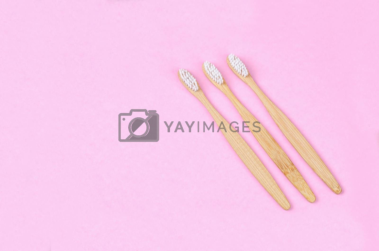 Bamboo toothbrushes on pink background with free space for your text or message.