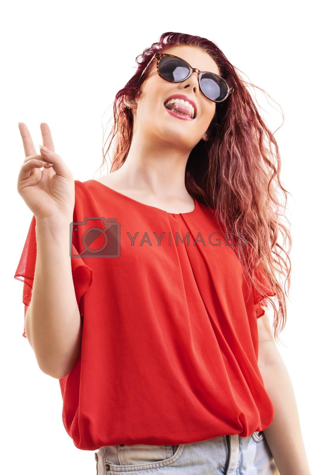 Bottom up view of a beautiful young redhead girl in a red blouse with sunglasses showing tongue, gesturing the peace sign, isolated on a white background.