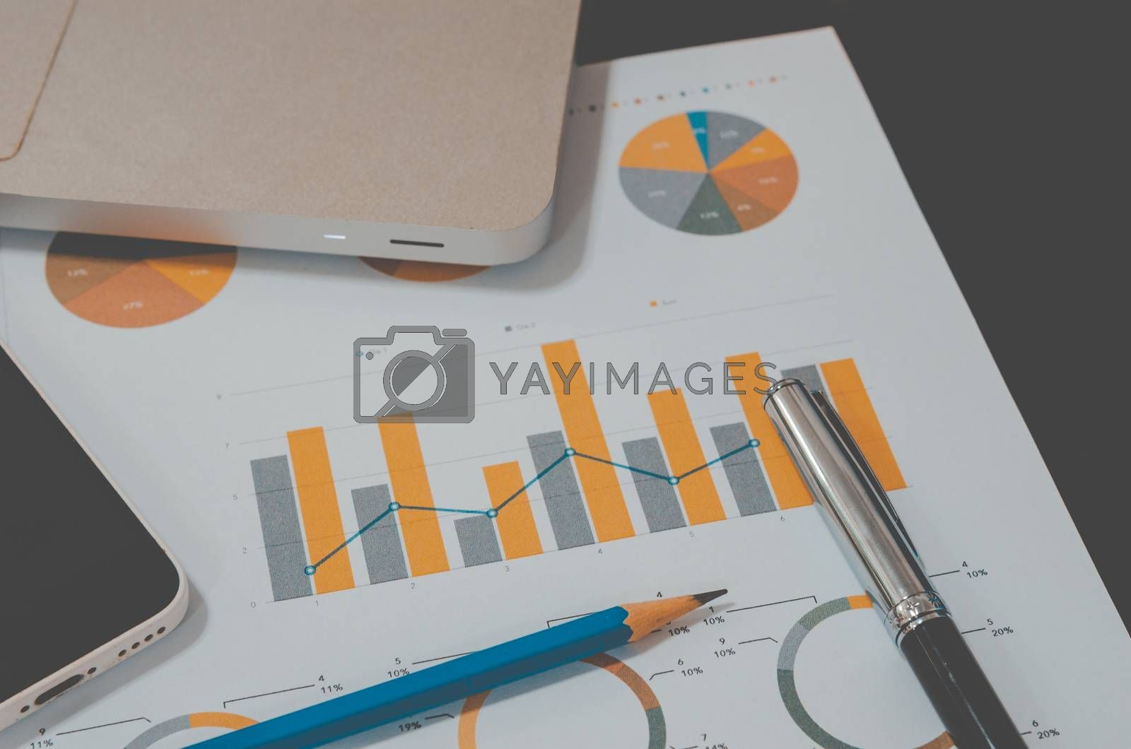 business documents graph financial and computer laptop on table with pencil and diagram. Vintage tone