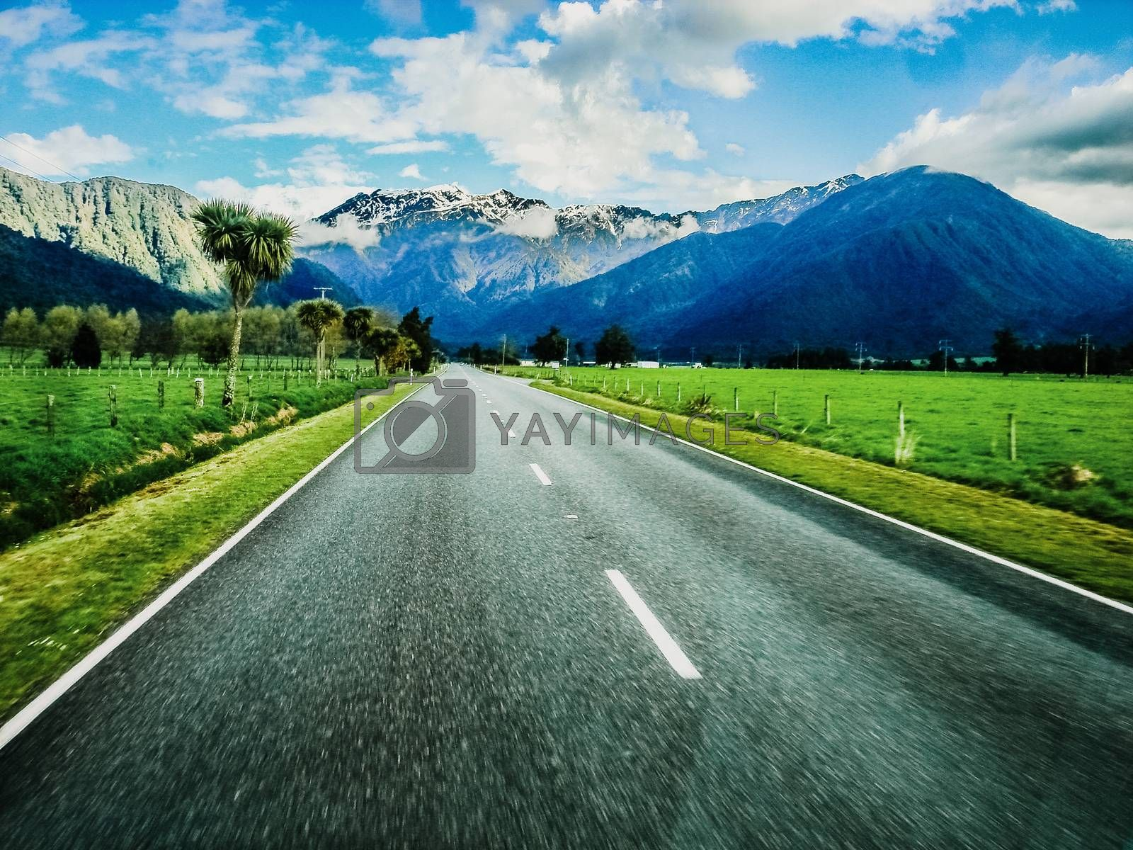 Mountain road with colorful landscape of high snowy summits to live adventures by car, unfocused edges to give impression of speed when driving.