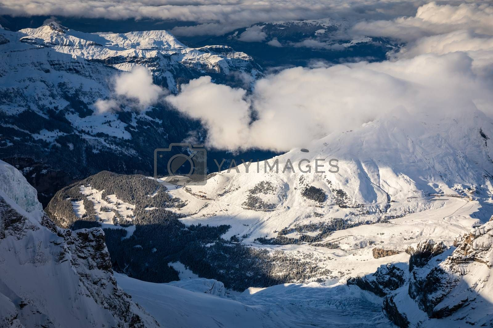 Aerial of snowcapped mountain range of Jungfrau before sunset on cloudy day in winter, view from Jungfraujoch in middle of Jungfrau and Monch, Interlaken, Switzerland.