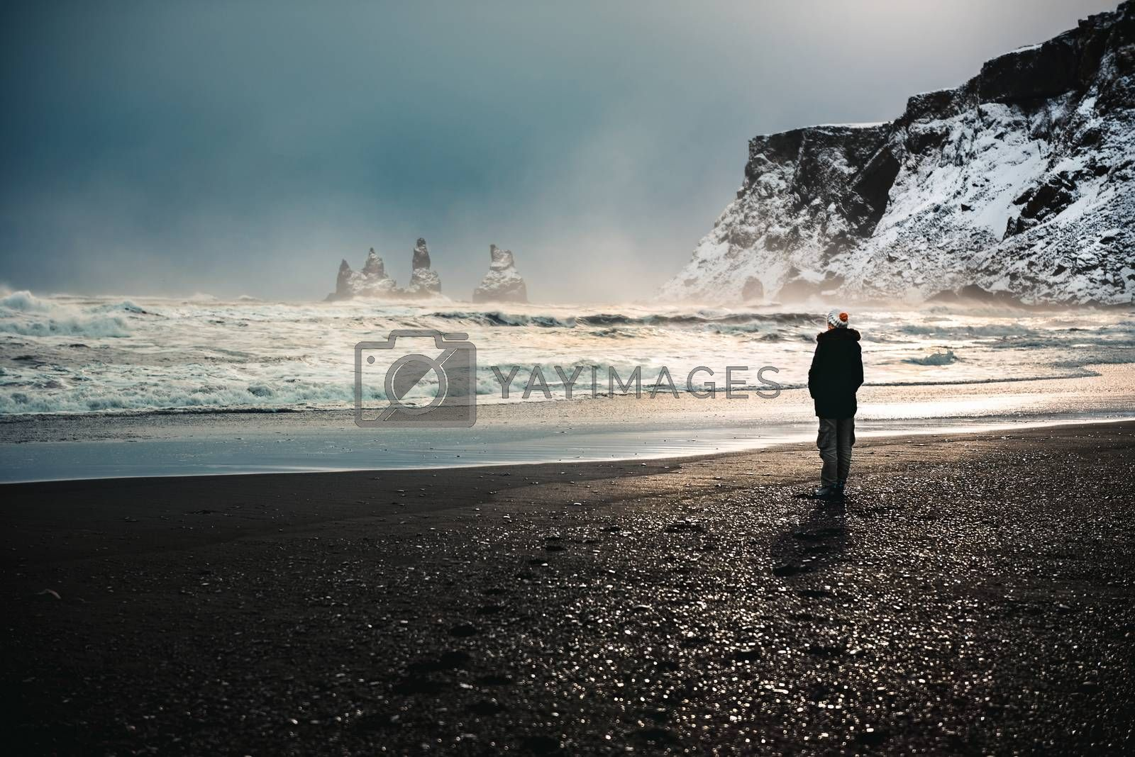 Traveler, woman standing on the black volcanic beach and enjoying amazing view on basalt sea stacks, Reynisdrangar in Atlantic ocean near Vik Myrdal, Iceland