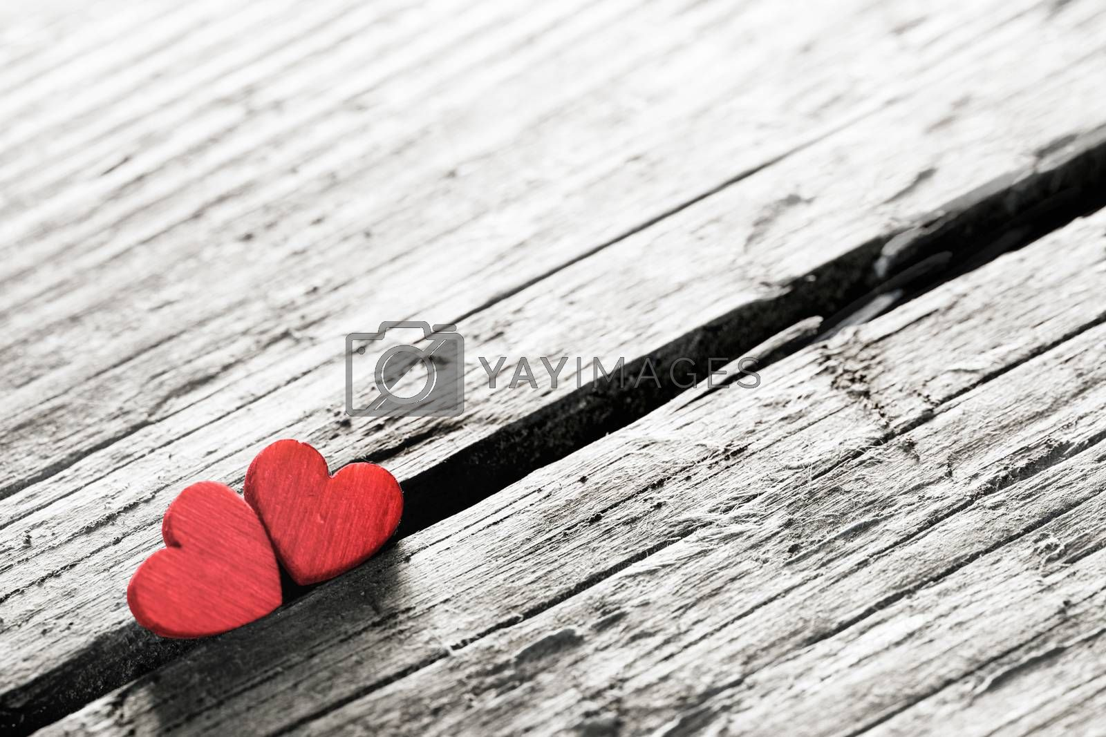 Two red handmade wooden carved hearts on wood background couple relationship Valentine day concept