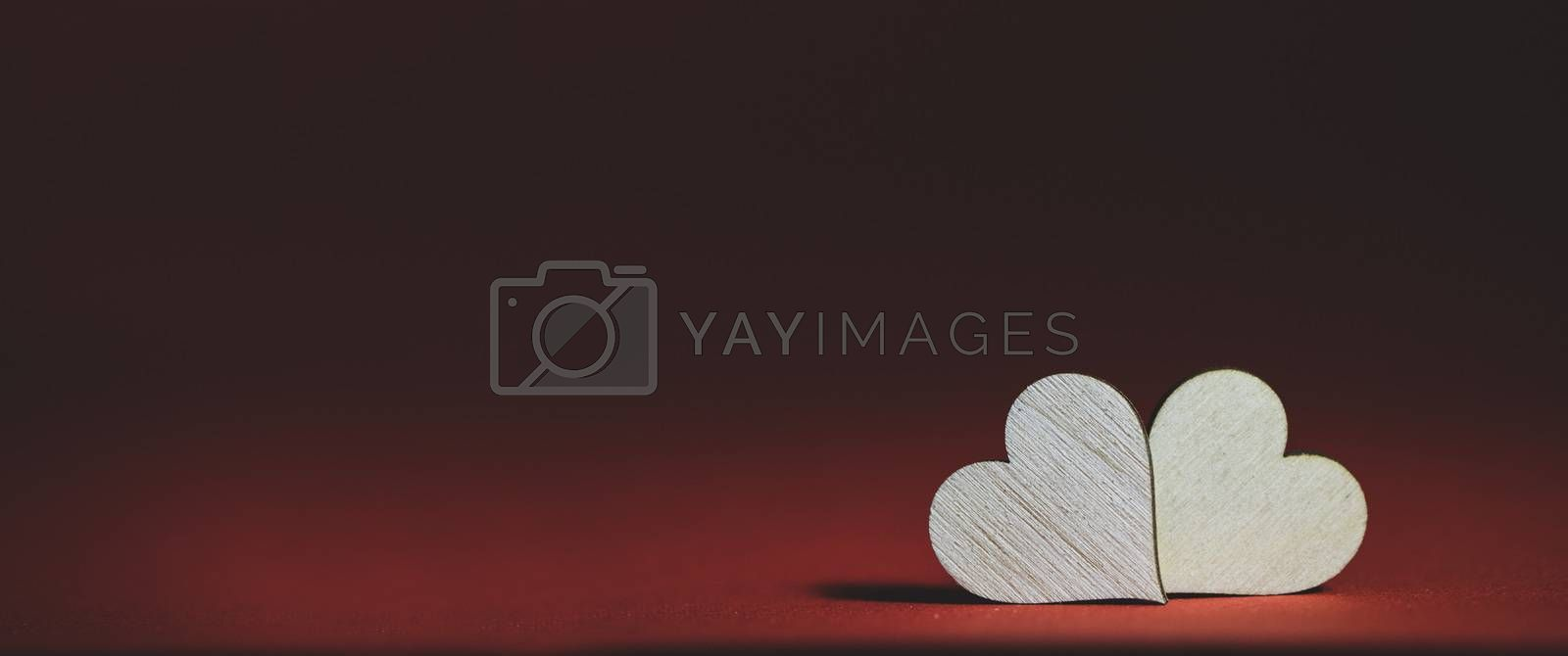 Two handmade wooden carved hearts on brown background couple relationship Valentine day concept
