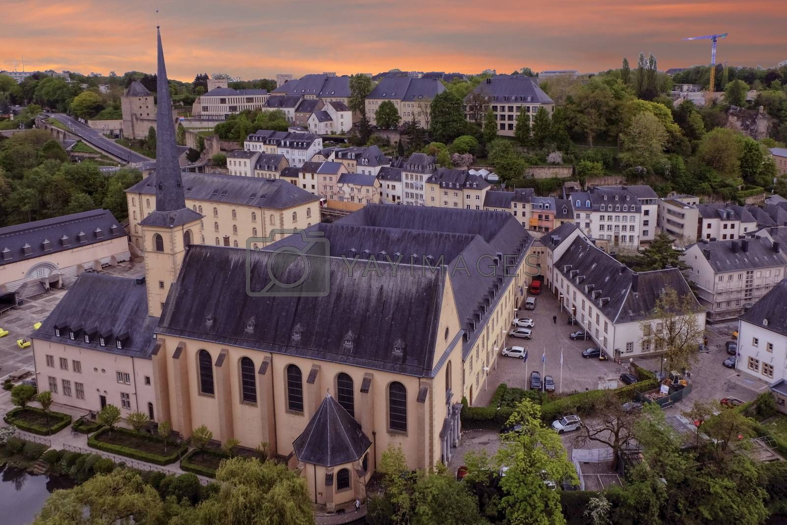 Alzette river, church of St Jean du Grund and Abbey de Neumunster in Old Town Luxembourg City from top view by sunset
