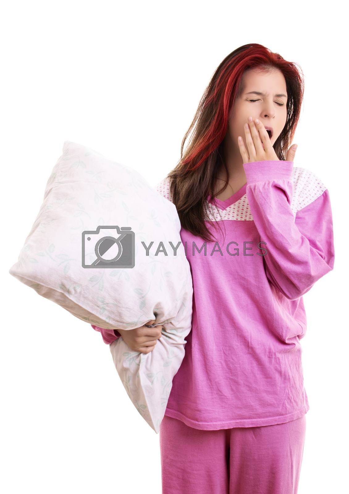 Tired young girl in pajamas holding a pillow and yawning by Mendelex