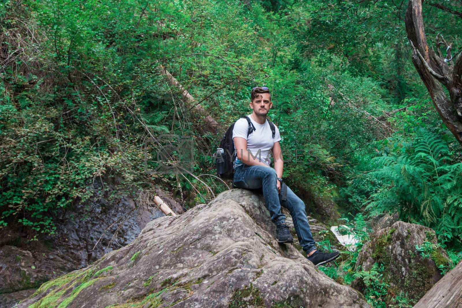 Man traveler with backpack sitting on rock in the forest. Travel lifestyle or adventure vacations concept