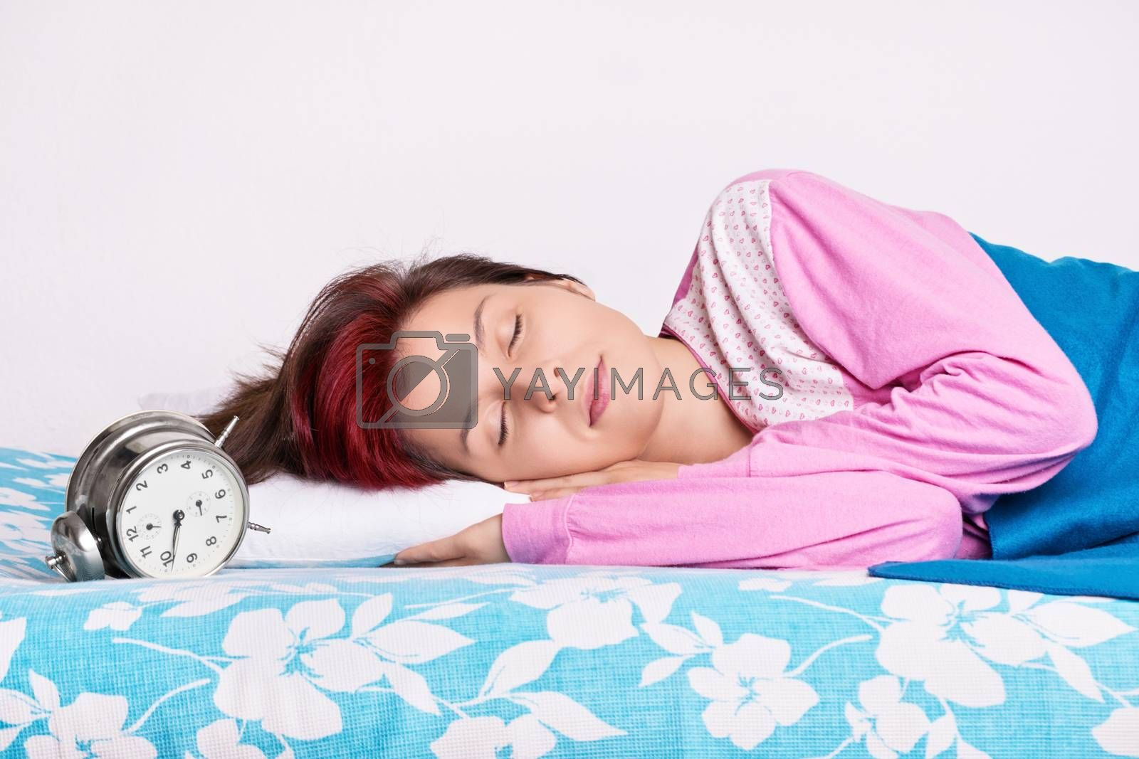 Girl in her bed sleeping next to the alarm clock by Mendelex