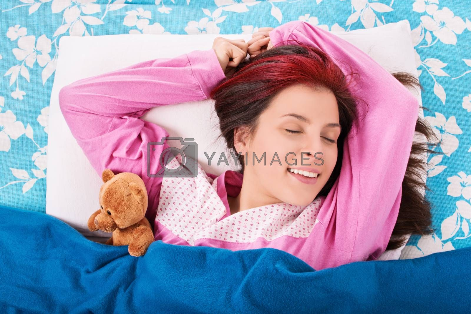 Smiling young girl sleeping with her teddy bear by Mendelex