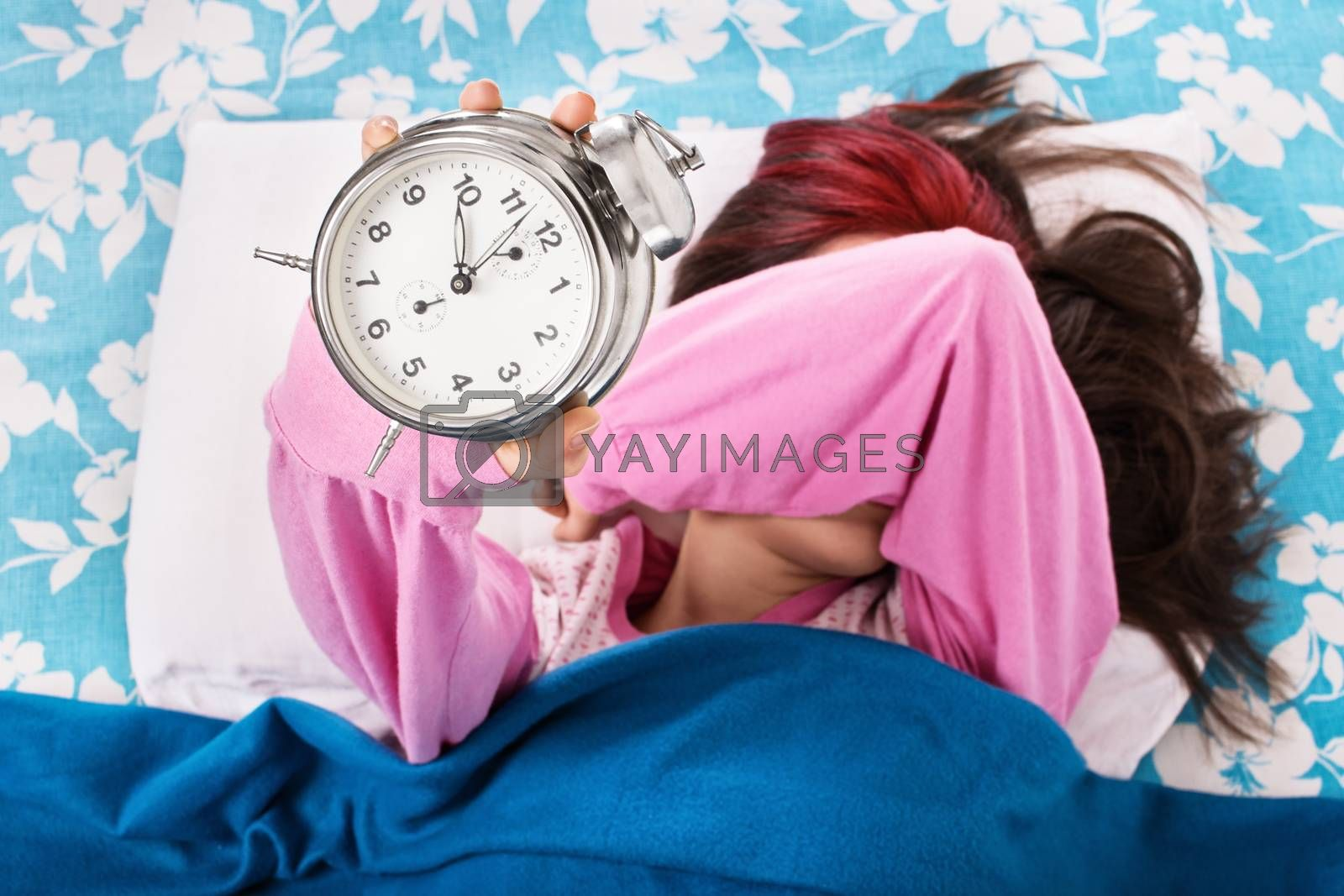 Young girl in bed covering eyes and holding alarm clock by Mendelex