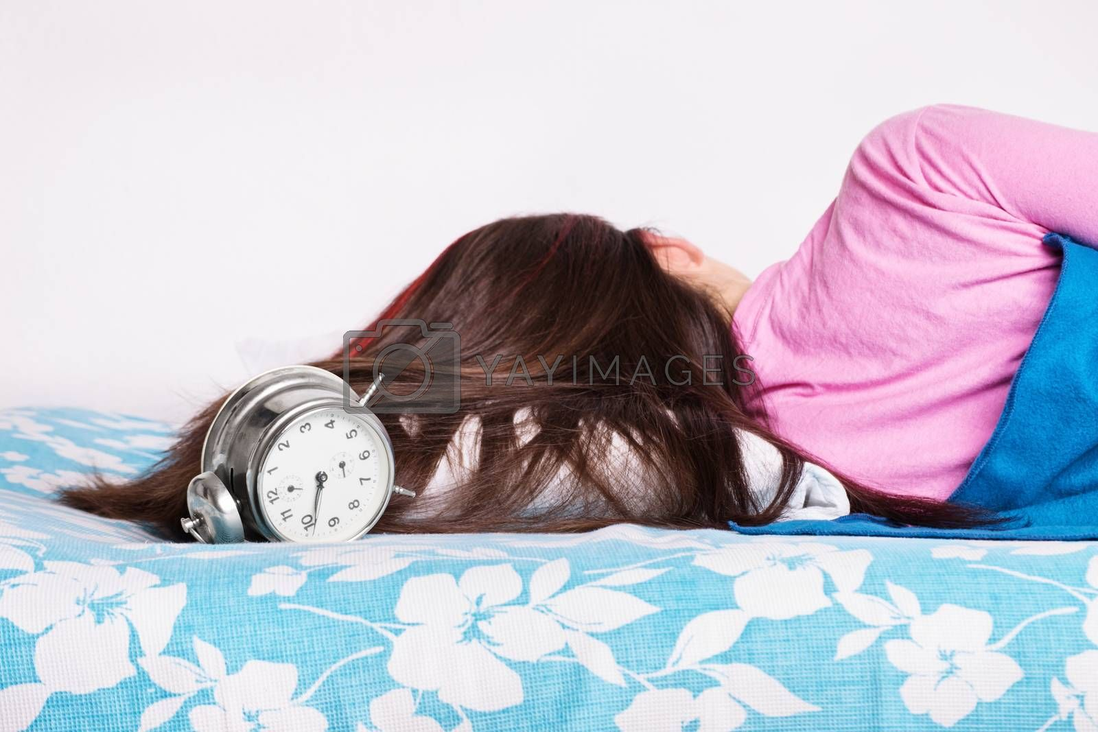 Young girl sleeping while the clock is ringing by Mendelex