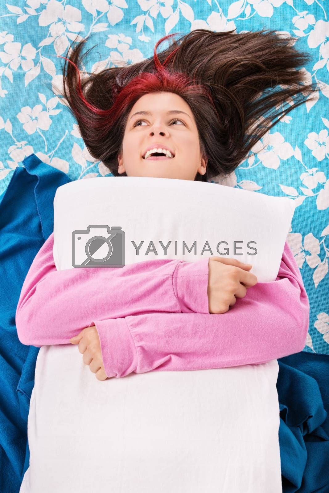 Young woman in bed smiling and hugging a pillow by Mendelex