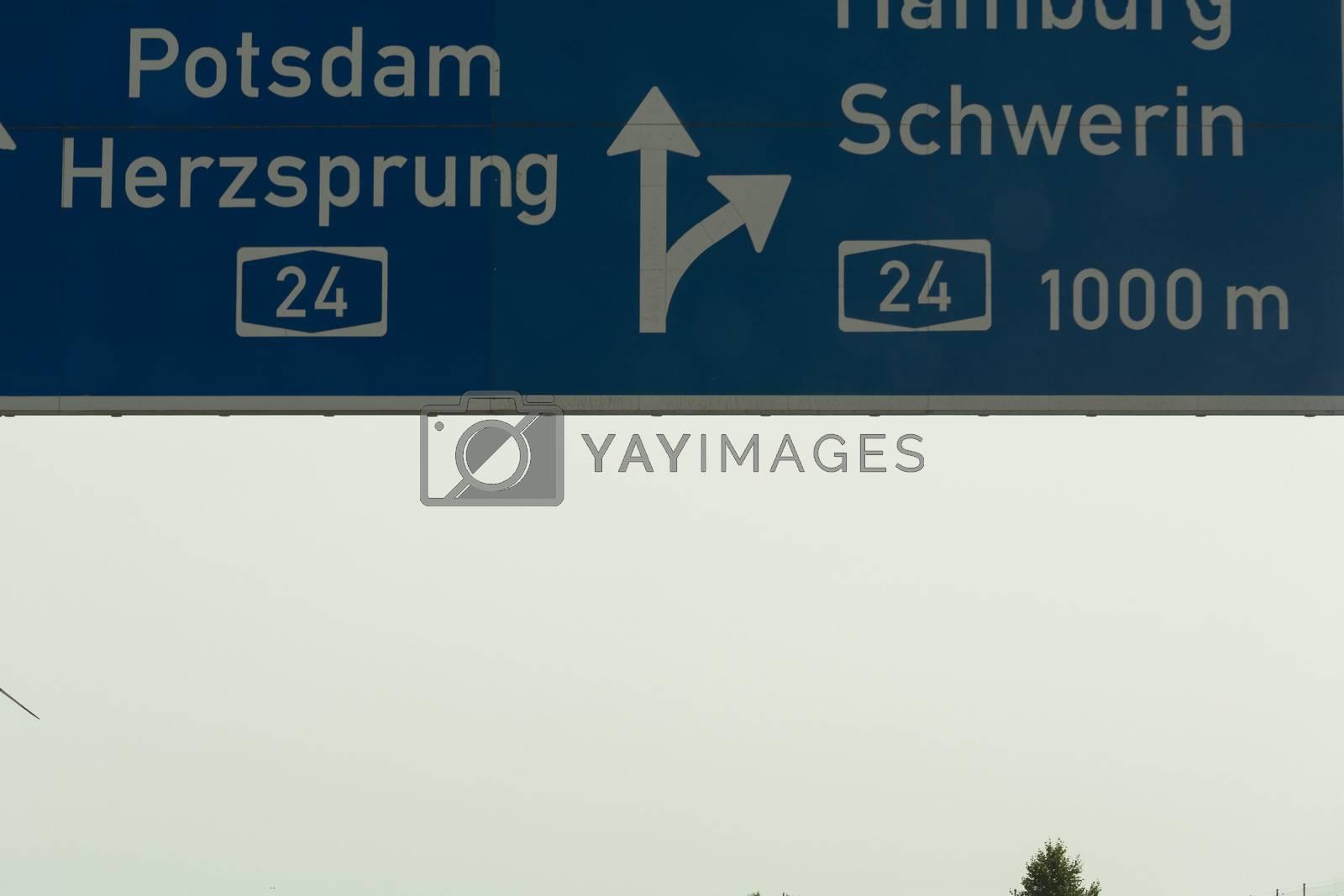 German motorway sign with inscription in German direction arrow to the cities - Berlin, Potsdam, Herzsprung, Hamburg and Schwerin