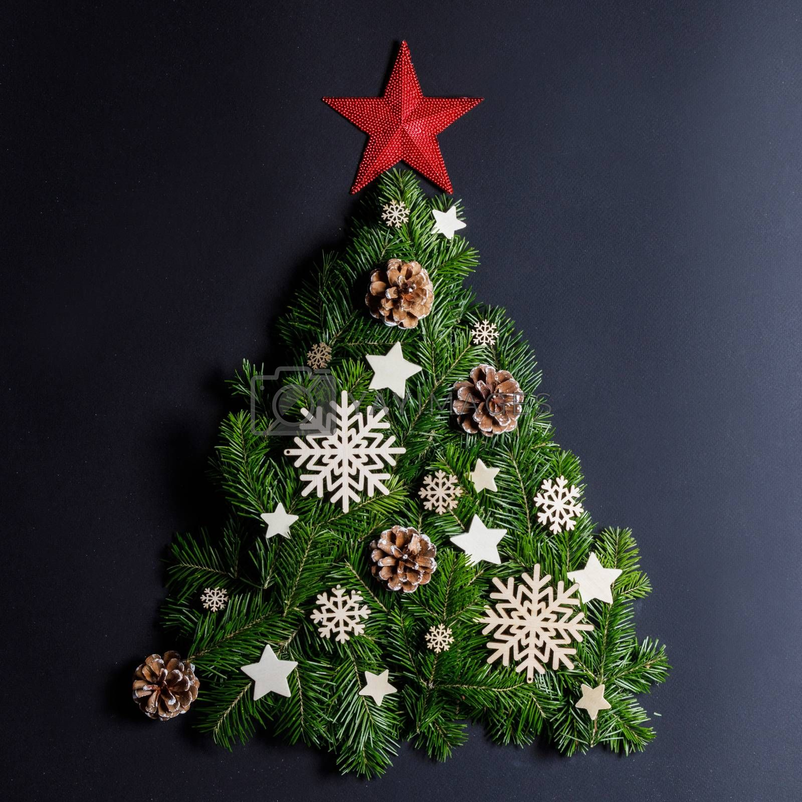 Christmas tree made of natural spruce branches deecor with red star on black background, flat lay card with copy space