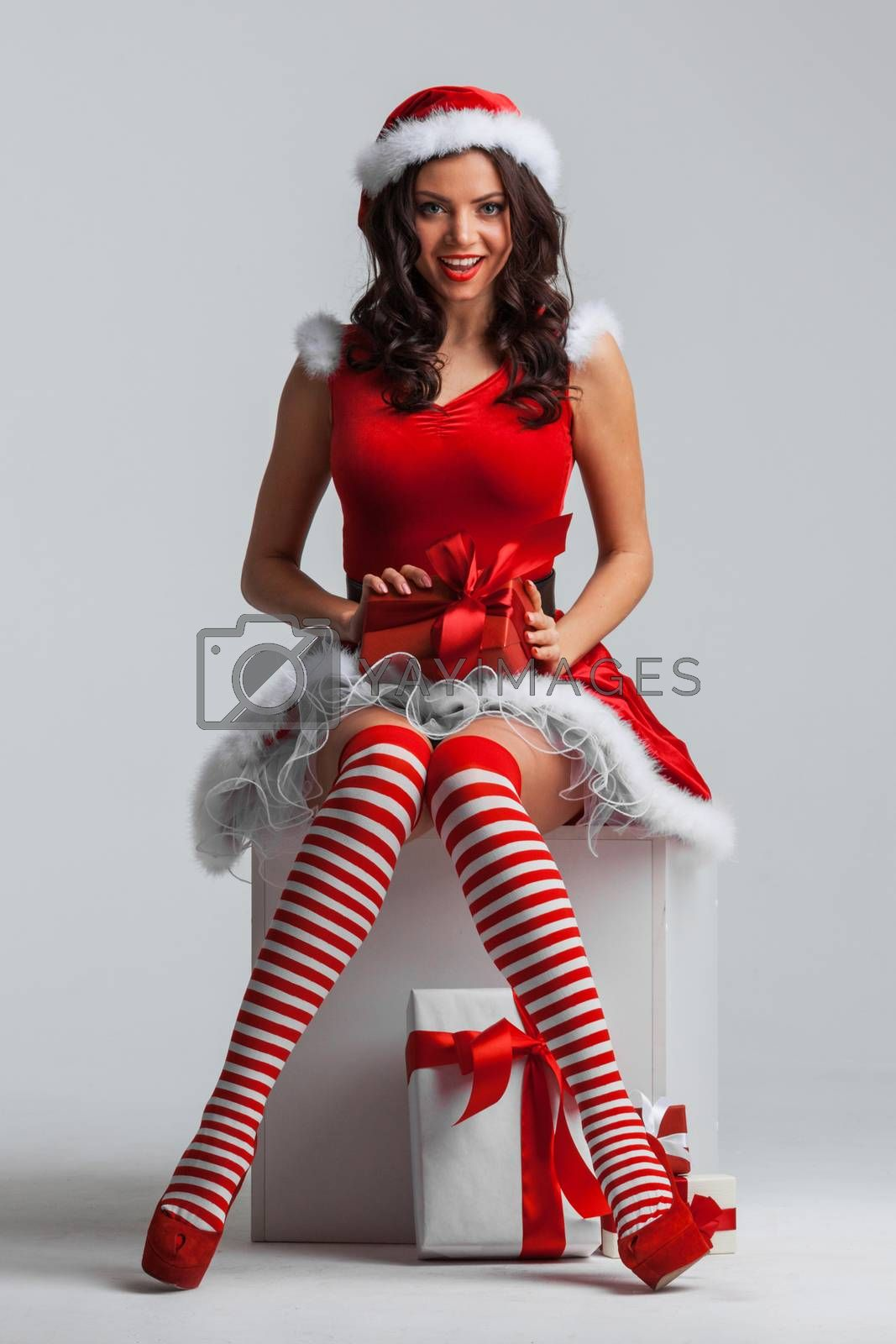 Beautiful young pin-up girl in santa dress unwrapping a christmas gift