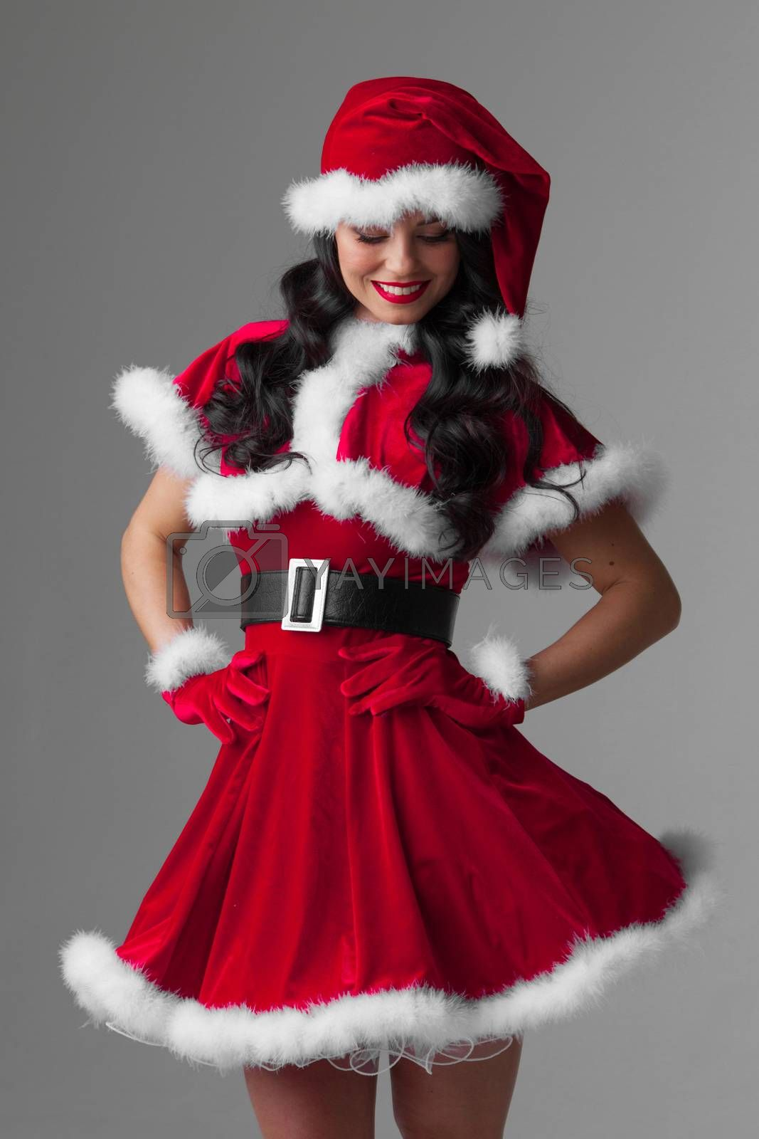 Beautiful woman in Santa Claus clothes on gray background