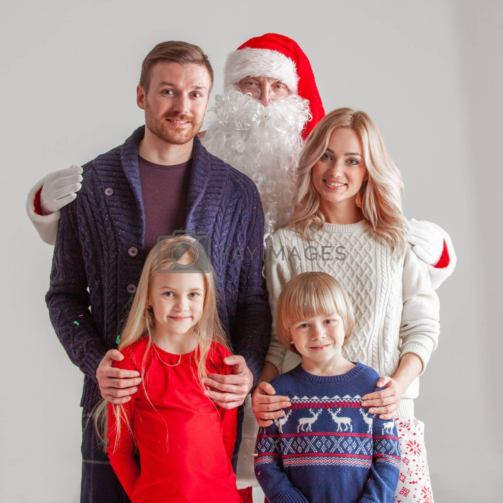 Christmas portrait of happy smiling family with two children and Santa Claus embracing them on gray background