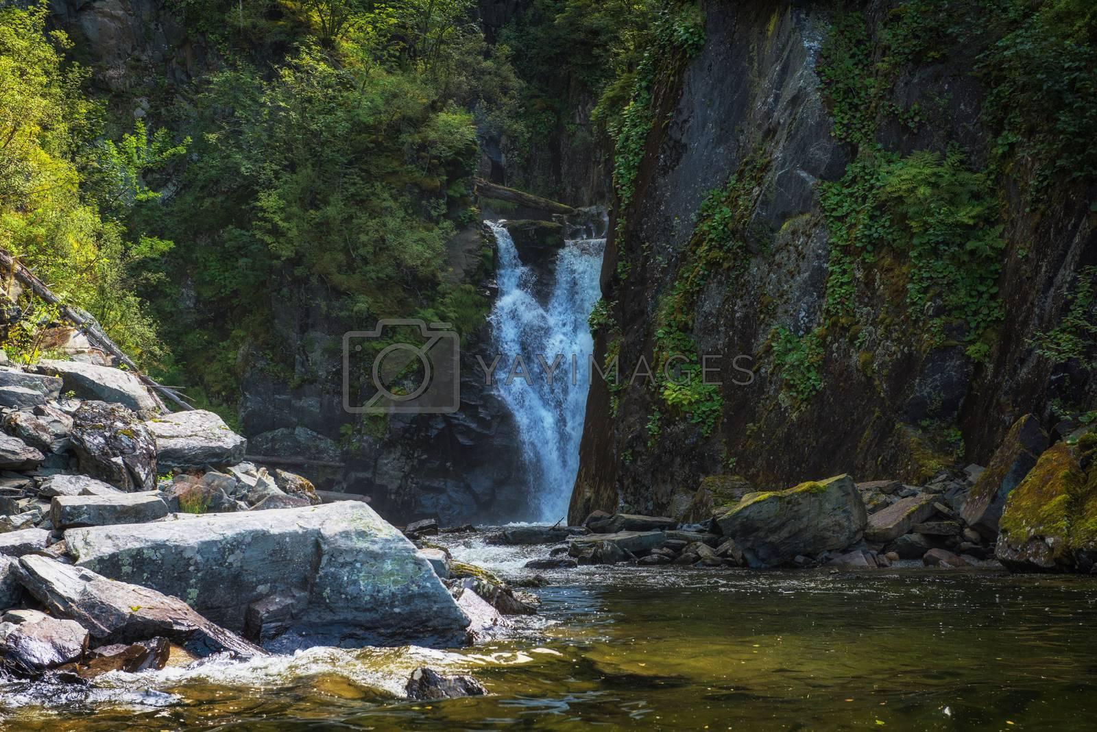 Kishte Waterfall at Lake Teletskoye in autumn Altai Mountains. The most famous lake waterfall