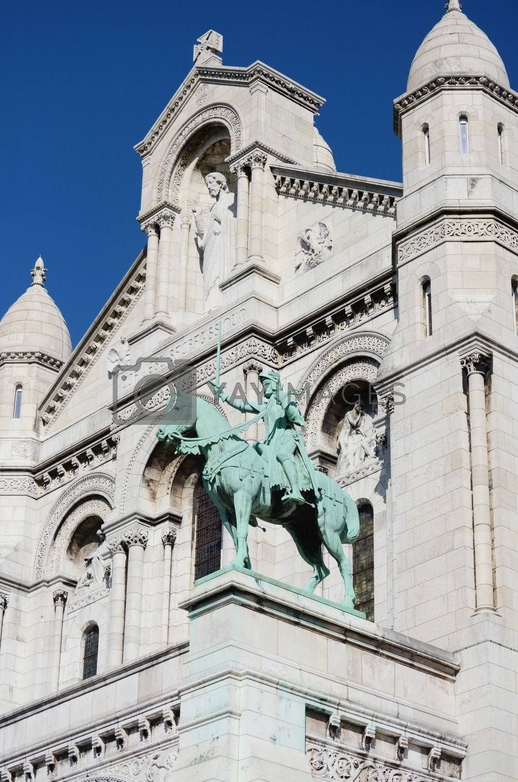 Joan of Arc bronze equestrian statue on the facade of the Sacre Coeur basilica, with the limestone architecture of the church beyond