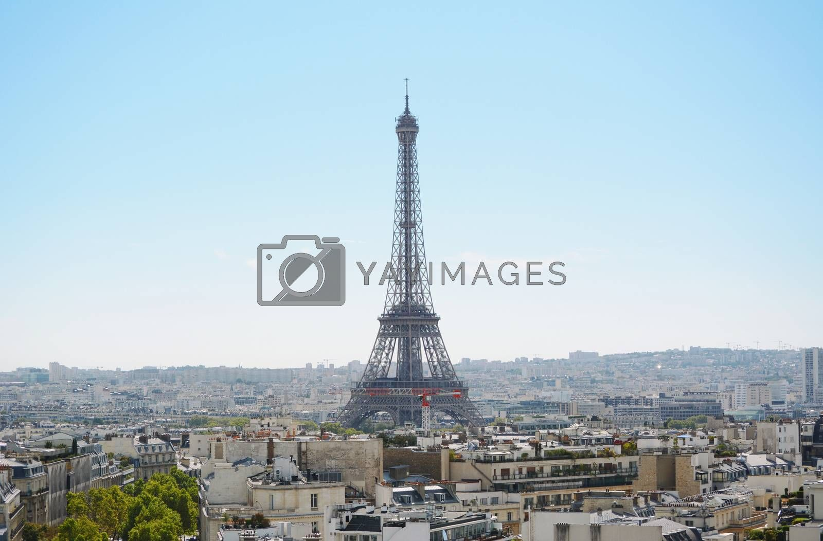 Eiffel Tower rises above the city of Paris, seen across the rooftops from the Arc de Triomphe