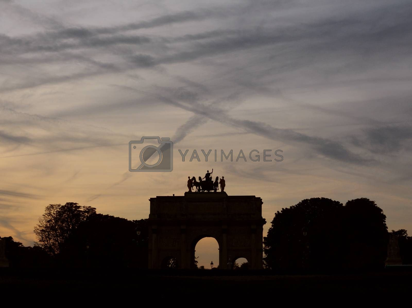 Arc de Triomphe du Carrousel near the Louvre in Paris in silhouette against a twilight sky covered in contrails