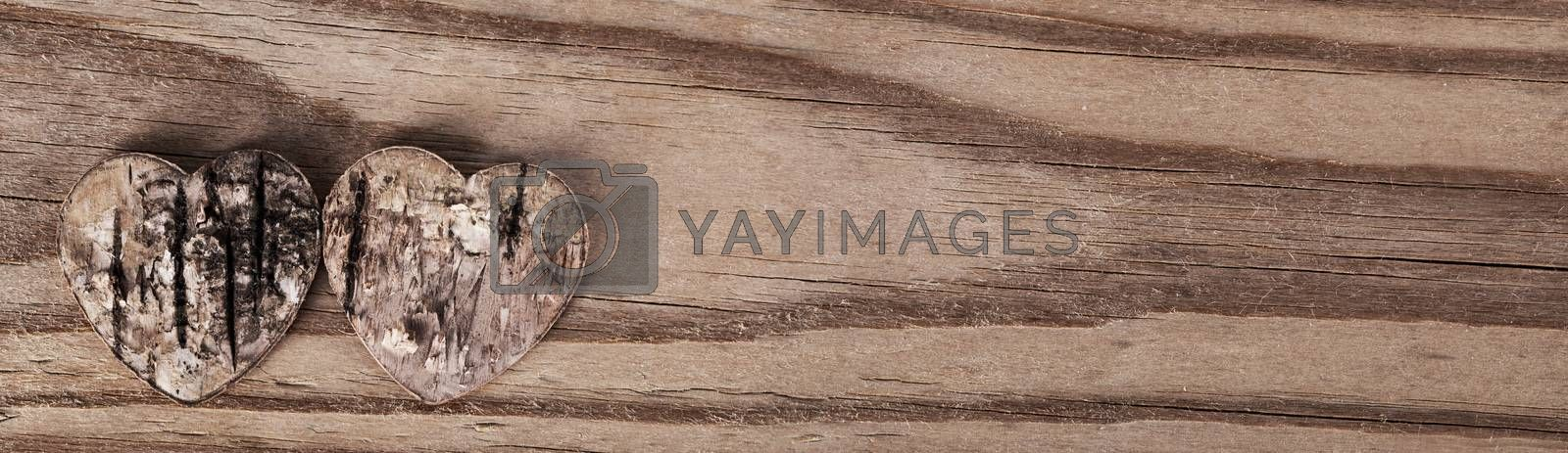 Two damaged rough rotten hearts on wooden background with copy space , love, Valentines day card