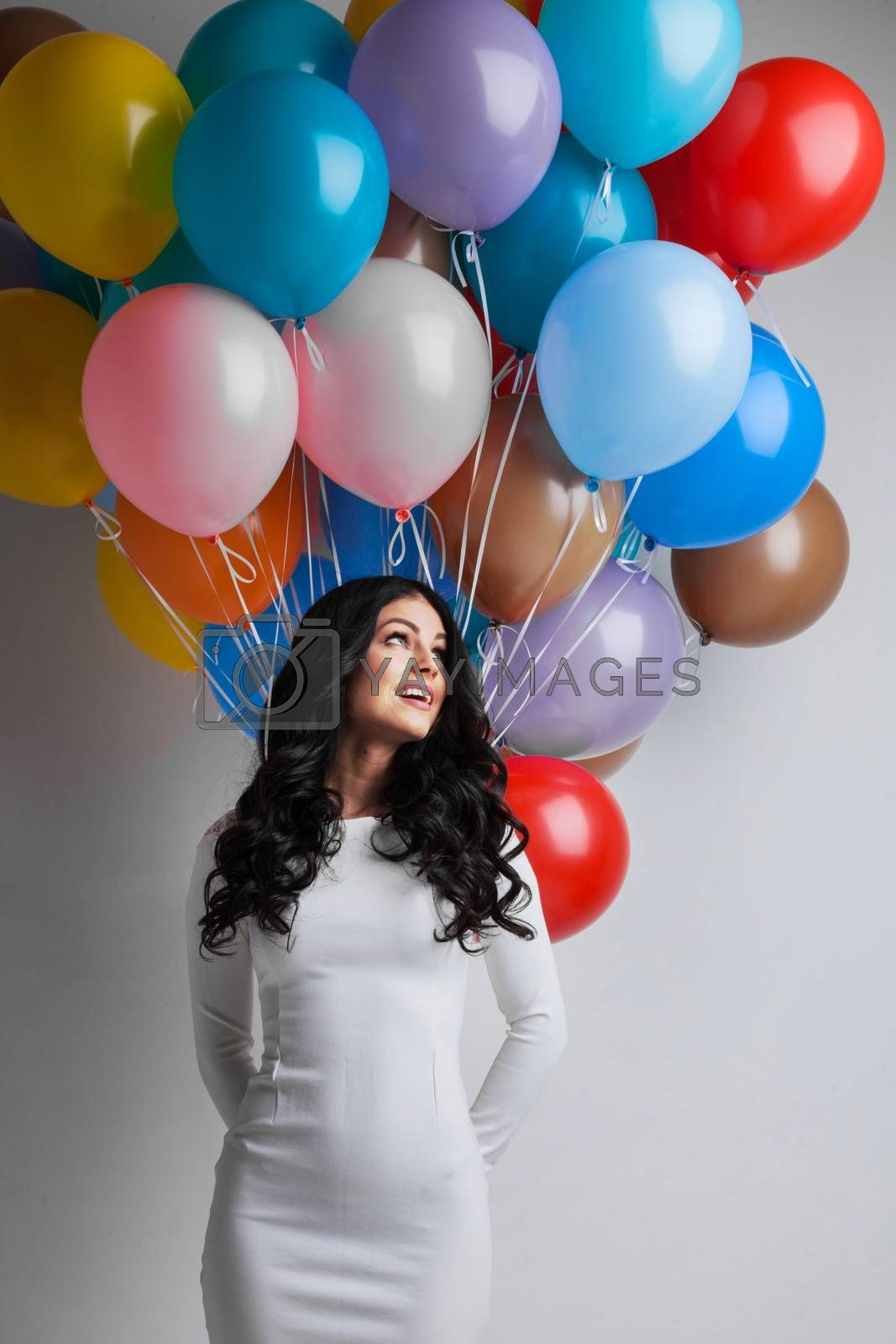 Young pretty woman in white dress with colored balloons on white background with copy space for text