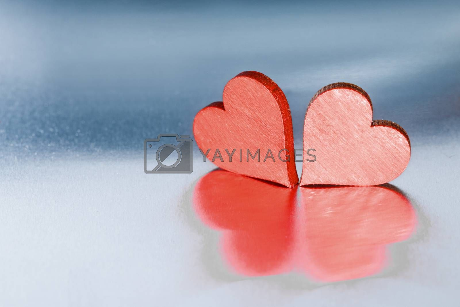 Two small handmade red wooden hearts on bright metal background Valentines day card