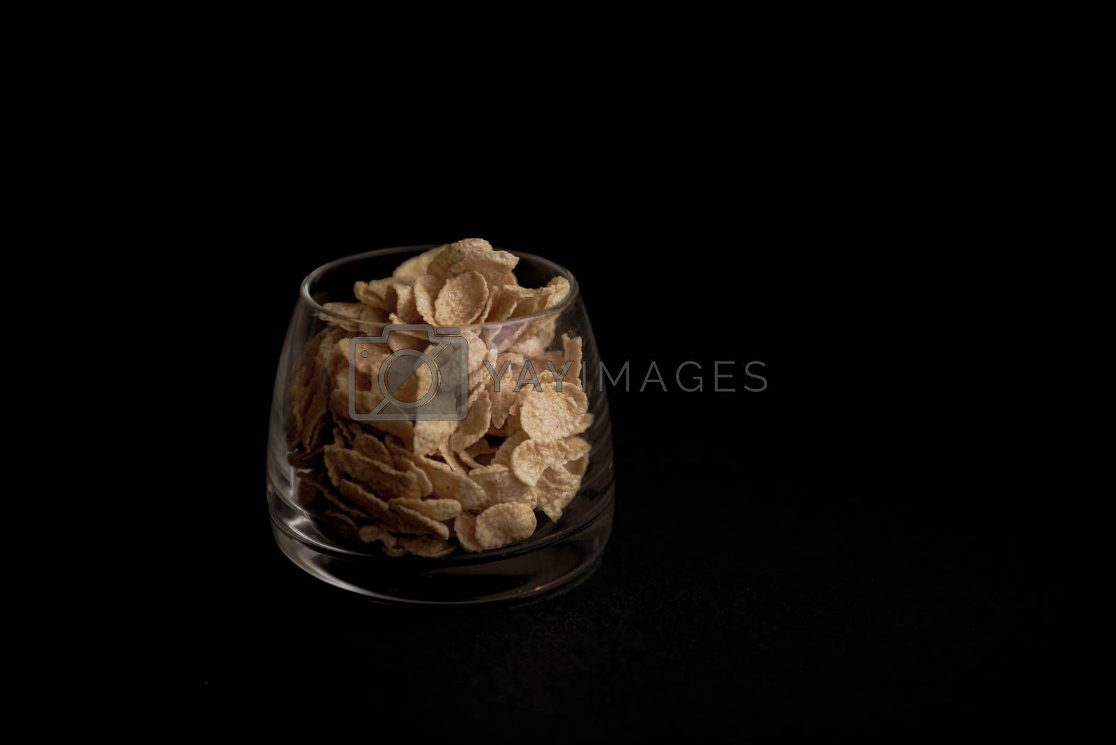 cornflakes in a transparent glass against a black background with place for text