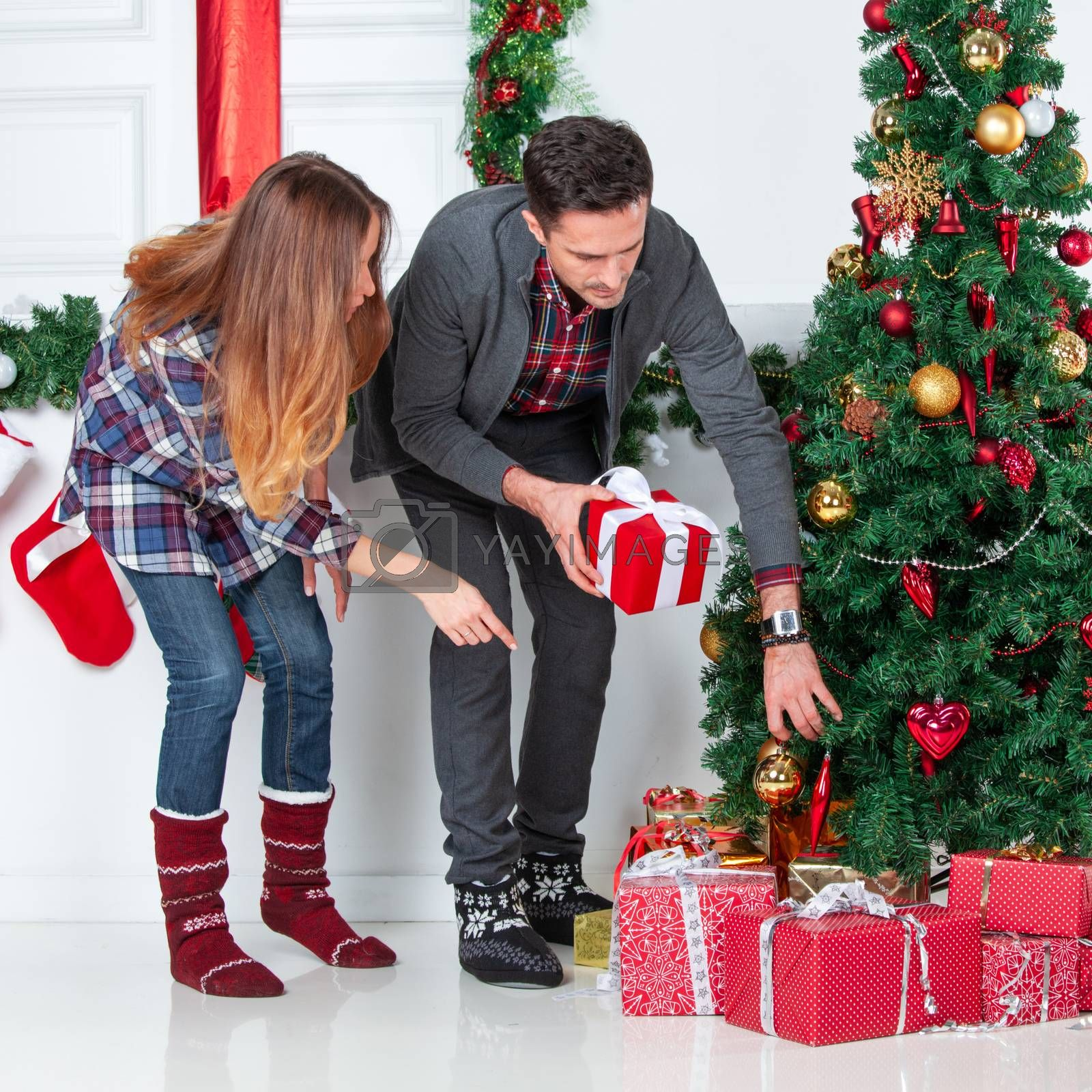 Happy parents put christmas gifts for children under decorated tree