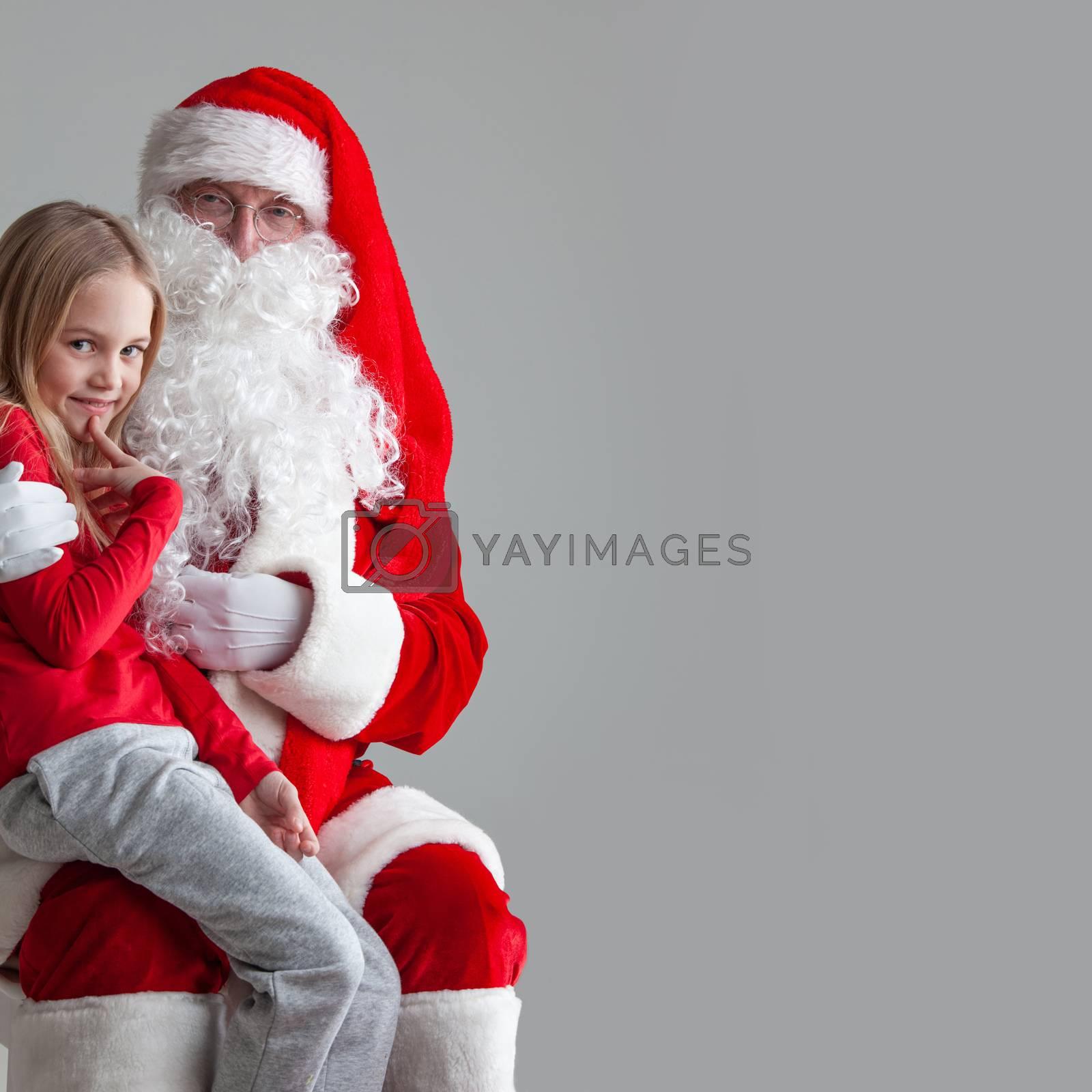 Portrait of smiling little girl sitting on santa claus knees near christmas tree