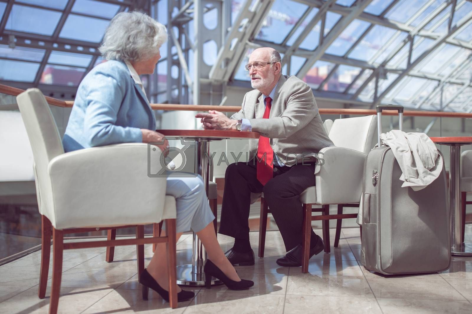 Happy elderly senior couple of travelers with suitcase in airport cafe waiting for flight