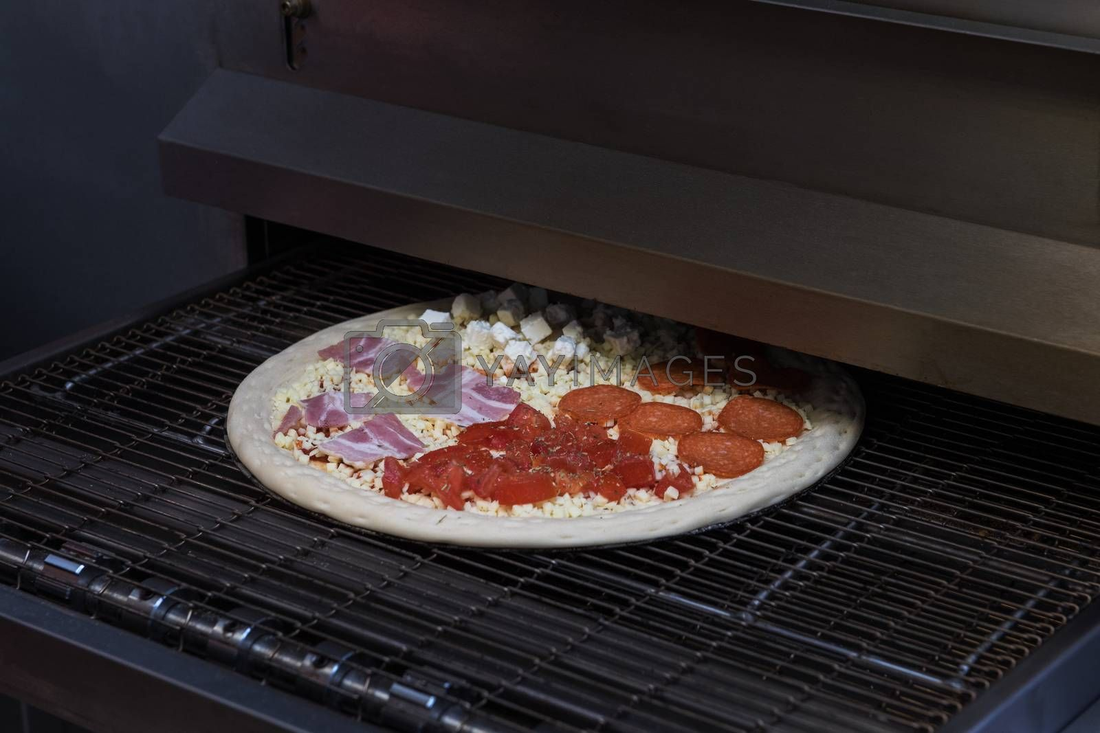 Preparing pizza in oven at restaurant kitchen