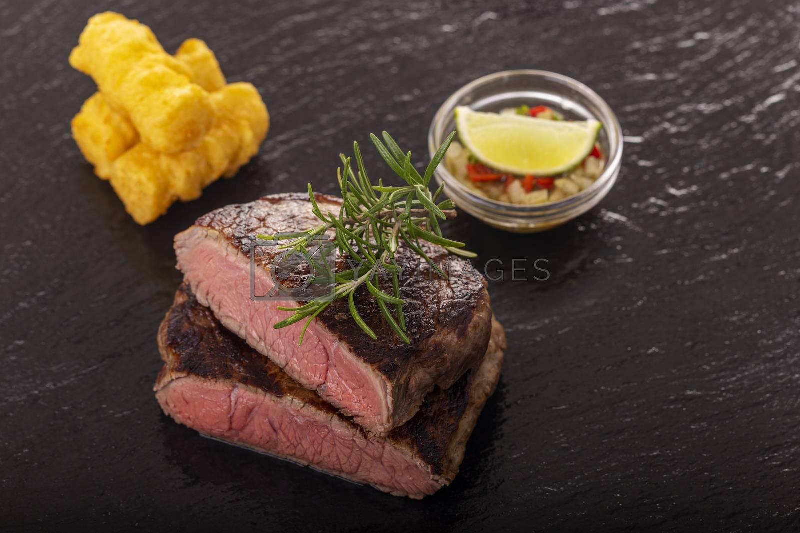 slices of grilled steak on black slate